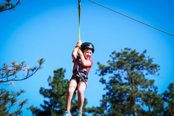 girl on zipline trees
