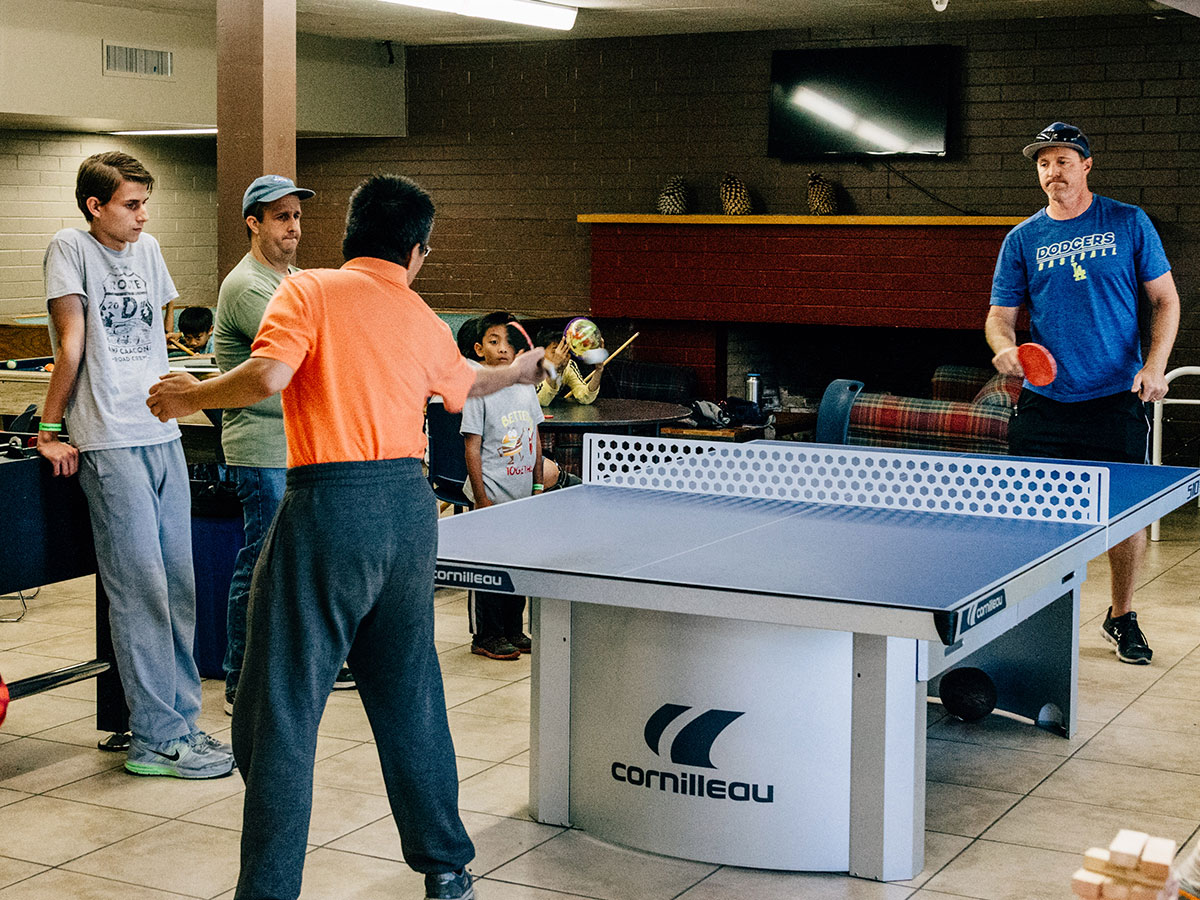 Family playing ping pong in the game room at Angeles Crest